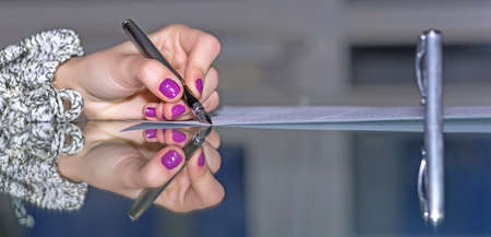 smothered: Woman hands working on paper document on glass office table making strong reflection with fountain pen stylish nail make-up soft smothered background cool tones Stock Photo