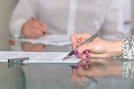 Female hand signing formal paper Close-up hand foreground working with paper sheet fountain pen male official dressed body on background glass office desk reflection