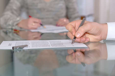 authorise: Male hand signing formal paper Close-up hand on foreground working with paper sheet fountain pen female body on background glass office desk with reflection