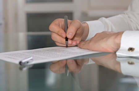 Businessman hands working on paper document on glass office table making strong reflection with fountain pen stylish shirt with golden cufflink soft smothered background