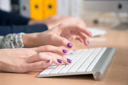 Female fingers typing on keyboard Office desk with keyboard and some other office supplies, female palms on the foreground, male hands on the background