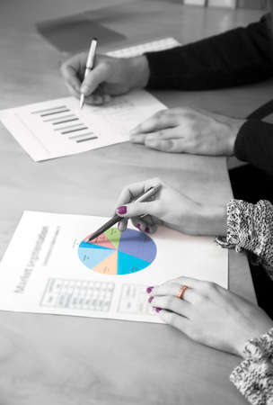 emphasise: Hands of male and female working on printed charts located on the office desk. Black and white background, but one chart and female nails and finger ring are colored Stock Photo