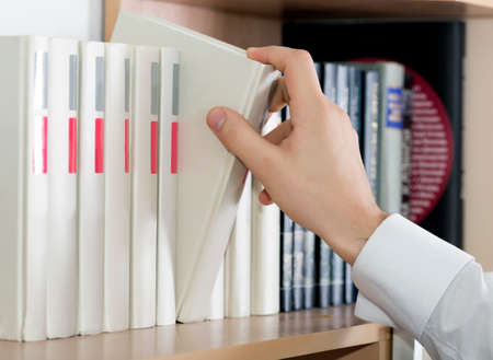 white sleeve: Choosing book Hand man white sleeve cuff shirt taking up grey book out of big range staying in row book shelf cupboard cabinet home interior