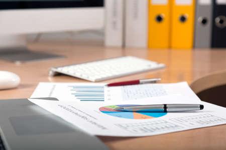 papeles oficina: Nos dej� el trabajo Vista lateral de lugar de trabajo con l�pices de colores gr�ficos impresos y port�til en primer plano cosechado grandes carpetas de pantalla y de oficinas en el fondo