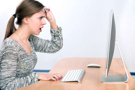 Angry lady yelling on computer screen Young beautiful lady expresses anger and fury sitting in front of large computer screen Smart casual dress, beige office desk, wireless keyboard and mouse, light grey background