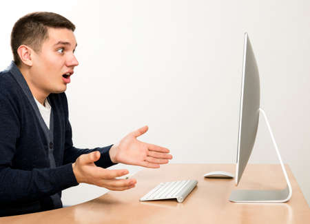 wtf: Young man expresses anger and fury sitting in front of large computer screen. Smart casual dress, beige office desk, wireless keyboard and mouse, light grey background