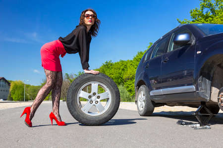 provocative: Leggy Lady dressed in provocative clubbing pantyhose and bright red shoes high heels mini skirt rolls large wheel to car fixed jack-screw some tools