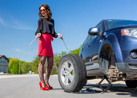 leggy: Leggy lady dressed in red miniskirt pantyhose high heels shoes stays next to broken car and keeping spare tire and tools Stock Photo