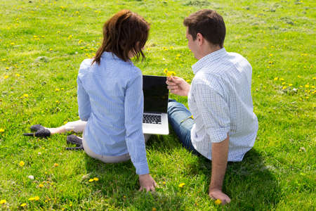 dress code: Man and woman casual dress code pant jeans shirt sitting on grass lawn working with laptop computer students learning businessman out of office from back