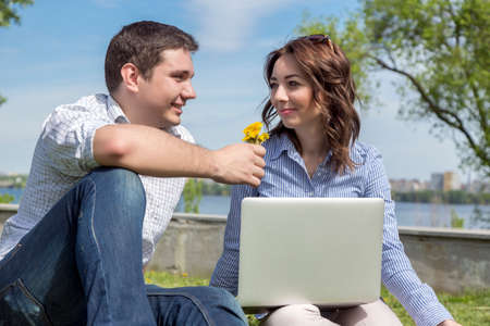 cute guy: Young cute male and female two people sitting in park with laptop computer casual dress code guy giving flowers to girl