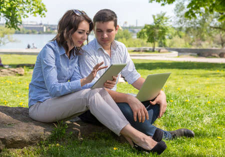 dress code: Young cute male and female two people sitting in park with laptop computer tablet PC casual dress code working together