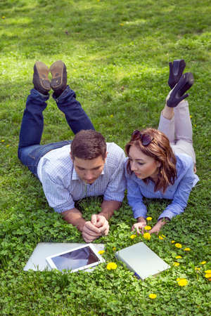 dress code: Man and woman casual dress code pant jeans shirt lying grass lawn working with laptop computer tablet PC book students learning businessman out of office Stock Photo