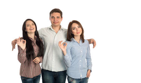 polygamy: Young man embracing two beautiful girls makes OK hand sign casual checkered shirts blue jeans lifestyle on white background