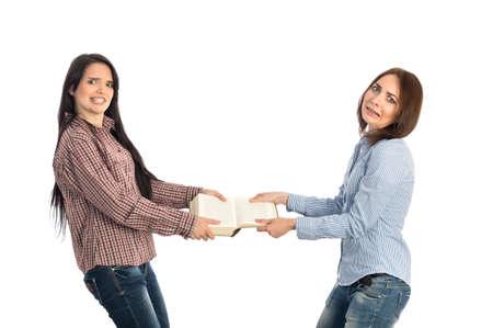 pelea: Dos mujeres jóvenes tira estilo antiguo libro grande hacia la otra tratando de romperlo casuales camisas pantalones vaqueros del código de vestimenta fondo blanco Foto de archivo