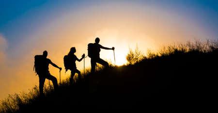 芝生の丘家族 3 人シルエット歩いて急な草が茂った丘の壮大な日の出と青い空を背景に登山