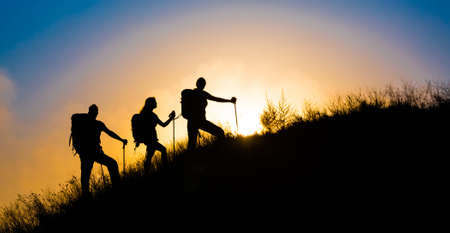 Climbers on grassy hill Family three people silhouette walking up steep grassy hill majestic sunrise and blue sky background 스톡 콘텐츠
