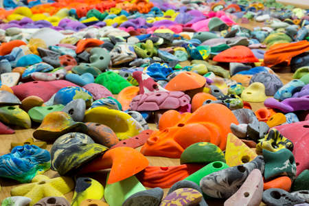 differ: Abstract composition with many large variety of colorful climbing holds for sport gym