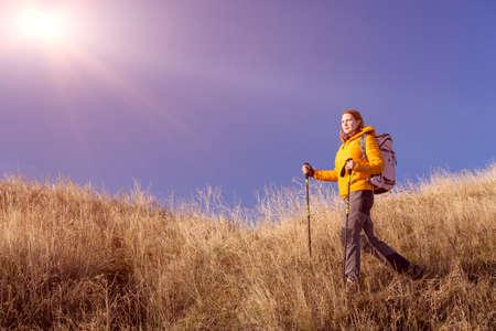 pantalones abajo: Mujer vestida chaqueta negro y pantalones grises con artes de senderismo paseos por cubierta de hierba amarilla de otoño cielo colina azul brillante sol de fondo Foto de archivo