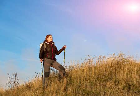 pants down: Woman dressed black down jacket and grey pants having trekking gear walks up towards peak across yellow autumnal grassy hill blue sky bright sun background