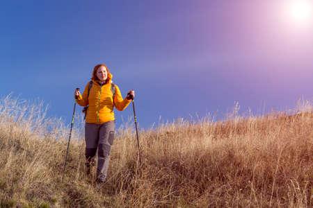 pantalones abajo: Mujer vestida de naranja por la chaqueta y unos pantalones grises que tienen engranaje de senderismo paseos de descenso a través de terreno cubierto de hierba cielo azul de fondo de otoño de color amarillo brillante sol Foto de archivo