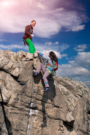 Two climbers reaching summit one drags rope assisting her partner to make last step young female athletes natural stone rock blue sky and shining sun 스톡 콘텐츠