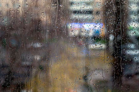 trickles: Rain drops on window - evening light Drops and trickles of water on glass surface, blurred urban background, colorful neon lights