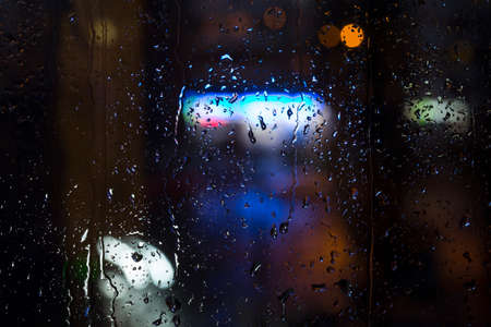 trickles: Rain drops on window - night light Drops and trickles of water on glass surface, blurred urban background, colorful neon lights
