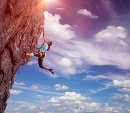 Elegant female athlete hanging at top of dangerous peak equipped with gear rope harness blue sky terrific clouds on background and sunbeams shining from above
