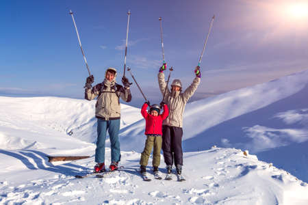 Winter sport family Family of three people - parents and little daughter - on winter mountains background happy laughing faces victory raised hands with  ski poles