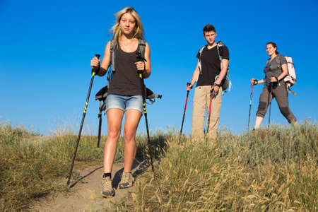 Three people two female one female heavy loaded with backpacks and trekking gear go along path throw wild grassy hill blue sky on background