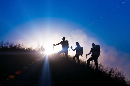 Group backpackers moving up toward grassy veld hill uprising colorful sun and rainbow clouds on background 스톡 콘텐츠