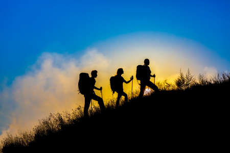 Silhouettes of three people walking with backpacks and other hiking gear up toward top wild grass mountain mother father daughter bright luminous sunrise sky background Foto de archivo