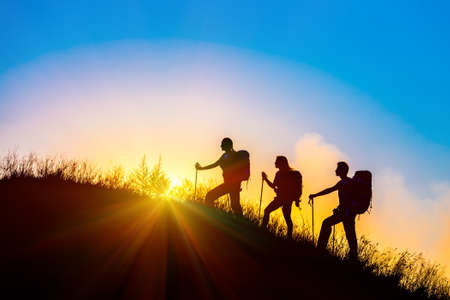Group of people silhouettes walking toward mountain summit with backpacks hiking trekking gear meeting uprising sun sunbeams and blue sky of background