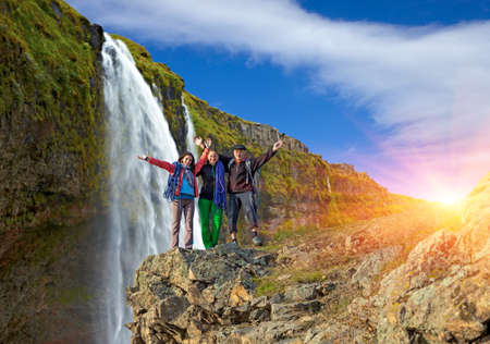 Grandparent and granddaughters embracing three people group tourists staying on rock mountain cliff large waterfall background rainbow colored sun and sunbeams cloud blue sky Stock Photo