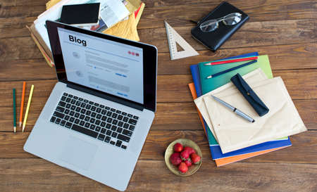 Very natural vintage looking working desk top view with laptop computer strawberry colorful booklets pen pencil glasses envelope other devises and business items stationery
