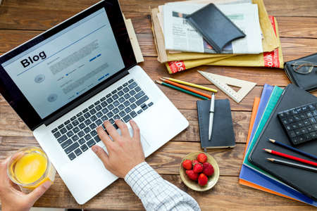 devise: Man typing on keyboard drinking juice at wooden desk with laptop newspaper magazines and plate of strawberry Stock Photo
