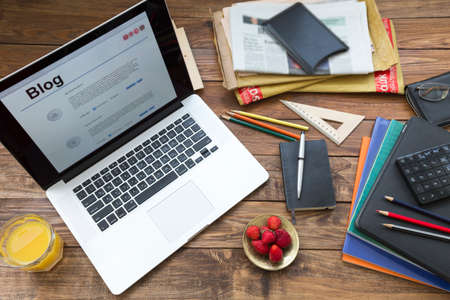 Home working space of creative person with laptop booklets, newspapers, other gadgets and office supplies, color pen and pencil Stock Photo