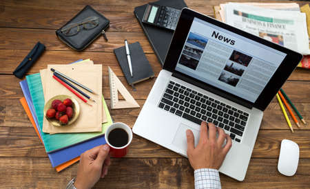 Countryside working room vintage wooden desk laptop digital news internet page opened screen man top view working keyboard drinking coffee mug business items creative mess