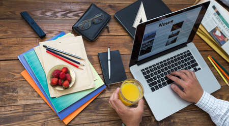 Man reading news at internet newspaper at sitting at wooden desk with papers, booklets pens office supplies and tools plate of fresh red strawberry