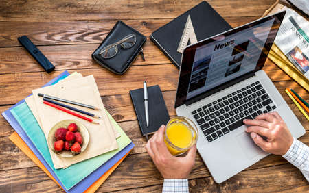 digesting: Man reading news at internet newspaper at sitting at wooden desk with papers, booklets pens office supplies and tools plate of fresh red strawberry