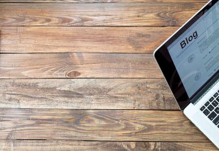 화면에 블로그 페이지와 거친 나무 책상과 자른 노트북 책상