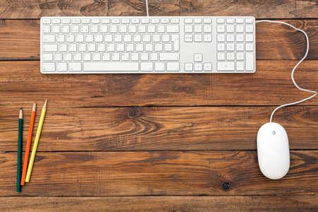 Vista desde arriba en el espacio de trabajo limpio, bien organizado en el estilo de la vendimia escritorio de madera en bruto naturales enmarcado por teclado de color blanco ratón lápices Foto de archivo - 48535604