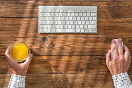 klawiatura: Czysta przestrzeń robocza na rocznika tabeli biznesmen gospodarstwa sok pomarańczowy szkła obliczeniową myszy i kostium pochodzących rzut żaluzje