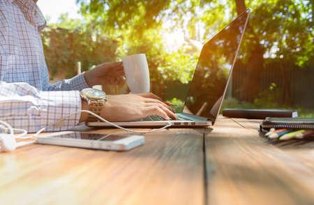 Smart casual gekleed persoon werken op de computer het drinken koffiemok zittend aan ruwe natuurlijke houten bureau buiten met groene boom en zon op de achtergrond Stockfoto