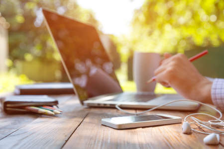 Freelance work Casual dressed man sitting wooden desk inside garden working on computer pointing with color pen drinking coffee gadgets dropped around table side view Standard-Bild