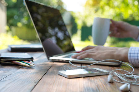 Business style dressed man sitting at natural country style wooden desk with electronic gadgets around working on laptop drinking coffee sunlight green terrace background