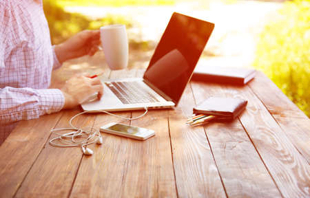 working out: Business style dressed man sitting at natural country style wooden desk with electronic gadgets around working on laptop drinking coffee sunlight green terrace background