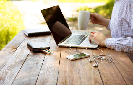 internet phone: Business style dressed man sitting at natural country style wooden desk with electronic gadgets around working on laptop drinking coffee sunlight green terrace background