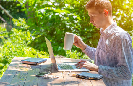 Smart casual dressed person working on computer drinking coffee mug sitting at rough natural wooden desk outdoor with green tree and sun on background