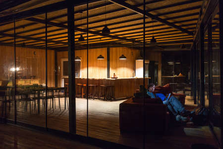 holidays vacancy: Empty Hotel Reception Desk at Night and People sitting at sofa working on Laptop faces illuminated by screens light wooden Building Country Style